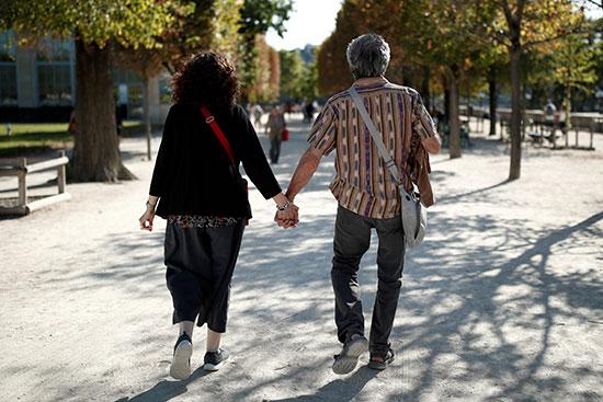 زوجان من كبار السن يسيران في حديقة التويلري
