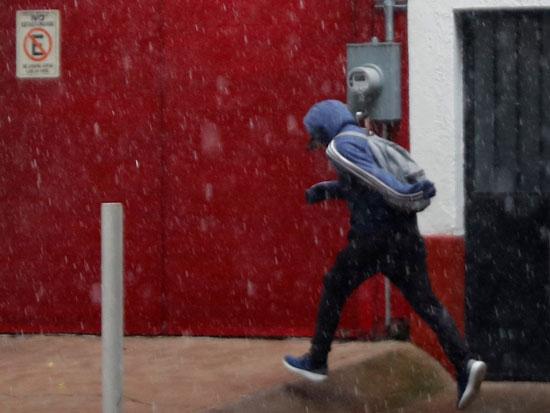 أحد-المواطنين-يهرول-هربا-من-الأمطار-المتساقطة