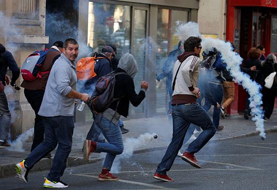 هروب المتظاهرين من الغاز المسيل للدموع