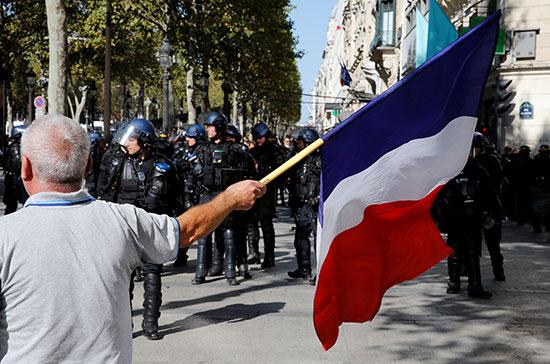متظاهر يرفع العلم الفرنسى