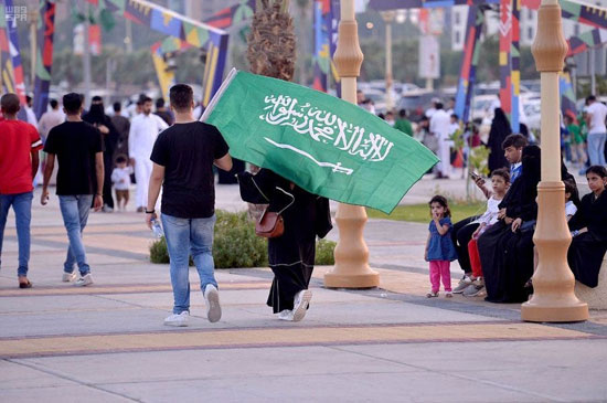 مواطنون-سعوديون-يحملون-علم-المملكة-اثناء-احتفالاتهم-باليوم-الوطنى