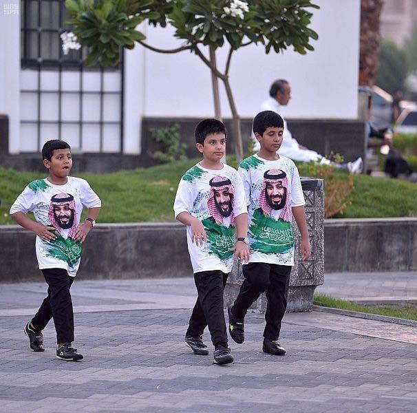 اطفال سعوديون يرتدون ملابس عليها صورة ولى العهد السعودى