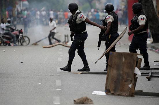 ضباط-من-الشرطة-الوطنية-الهايتية-وفى-المقابل-المتظاهرون