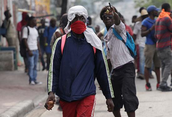 متظاهر-ملثم-يسير-وهو-يحمل-صخرة-أثناء-احتجاج