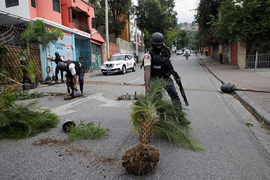ضابط-بالشرطة-الوطنية-الهايتية-يقوم-بمسح-النباتات-ملقاة-في-أحد-الشوارع