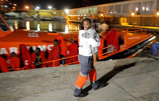 ناشطة فى الصليب الأحمر تحمل طفل بعد إنقاذه