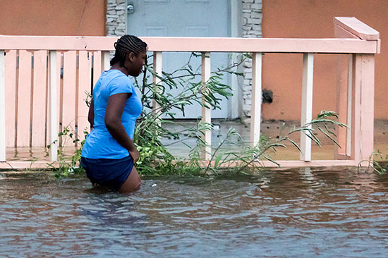 سيدة تسير فى مياه الإعصار