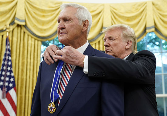 Trump puts the medal on the basketball player's chest