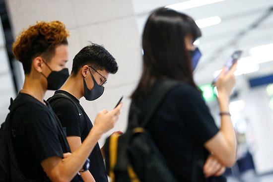 محتجون يتابعون الأخبار عبر هواتفهم المحمولة