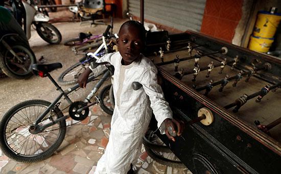 طفل يقف بجوار لعبته ودراجته فى داكار