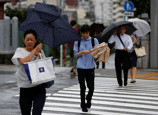 مواكنون يحملون المظلات للحماية من مياه الامطار