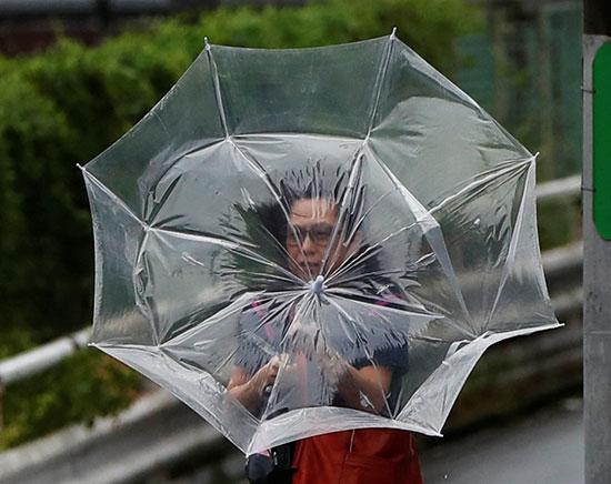 مواطن يحمل مظلة للحماية