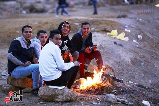 شباب يشعلون بقايا الاخشاب للتدفئه