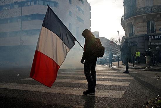 متظاهر يرفع علم فرنسا أثناء المظاهرات
