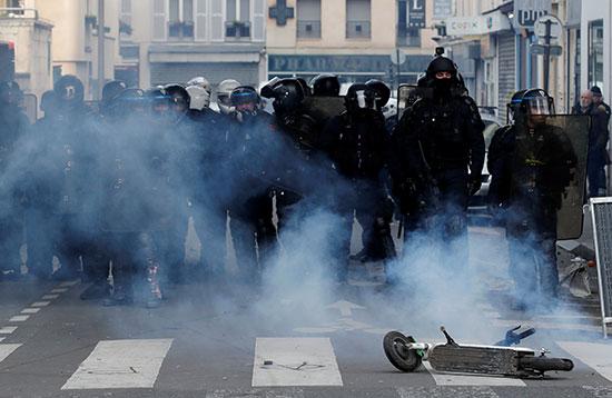 شرطة مكافحة الشغب تقف وراء سحابة من الغاز المسيل للدموع خلال مظاهرة مع أعضاء النقابات العمالية والعمال الفرنسيين
