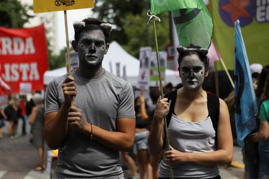 المتظاهرون يرفعون لافتات الاحتجاج