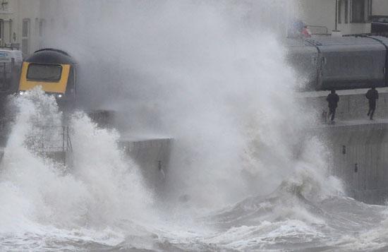 موجات كبيرة تضرب جدار البحر أثناء تحرك قطار وسط العاصفة بريندان