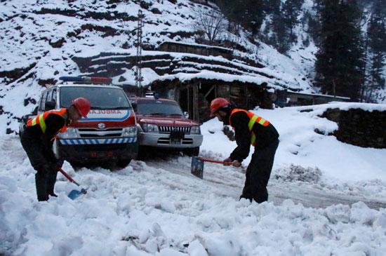 عمال الإنقاذ يقومون بإخلاء الطريق المغطى بالثلوج لإفساح المجال أمام سيارة إسعاف