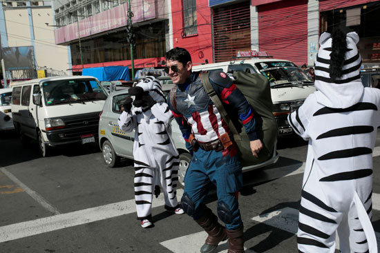 يمزحون مع رجل يرتدي زي شخصية الكتاب الهزلي كابتن أميركا في أحد شوارع لاباز