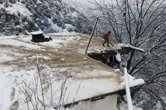 طفل يزيل الثلوج التى تغطى سقف منزله