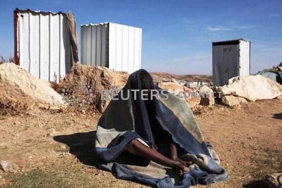 رجل-يجلس-على-الارض-بجوار-المخيم