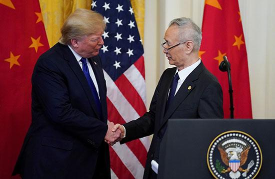 ترامب يصافح نائب رئيس مجلس الدولة الصيني ليو خه خلال حفل التوقيع