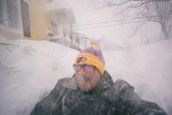 رجل يسير وسط الثلوج