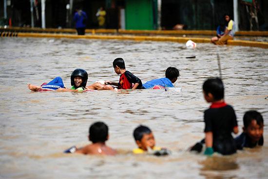 50670-أطفال-يلعبون-في-مياه-الفيضان-التي-ضربت-منطقة-جاتنيجارا-بعد-هطول-أمطار-غزيرة-في-جاكرتا