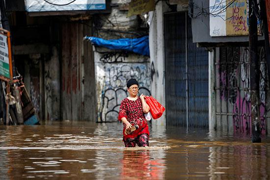 63969-امرأة-تحمل-متعلقاتها-تسير-عبر-مياه-الفيضان