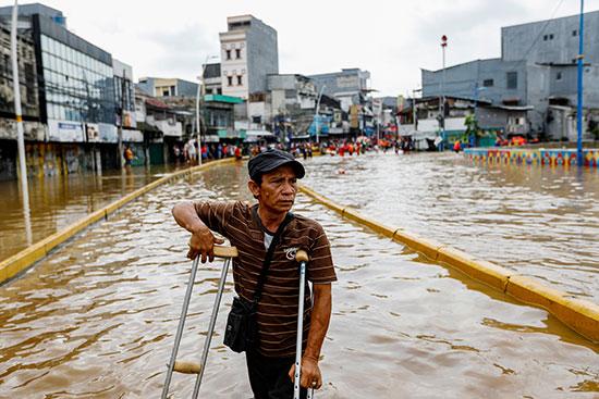 75604-رجل-يستخدم-العكازات-للمشي-في-مياه-الفيضان