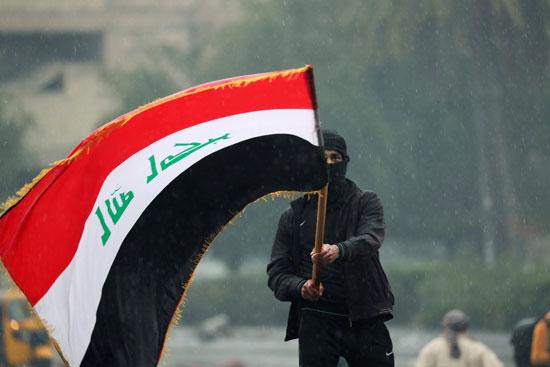 أحد المتظاهرين يرفعون علم العراق
