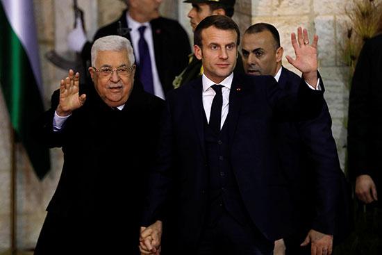 الرئيس ماكرون والرئيس عباس يلوحون وهم يرفعون أيديهم في رام الله