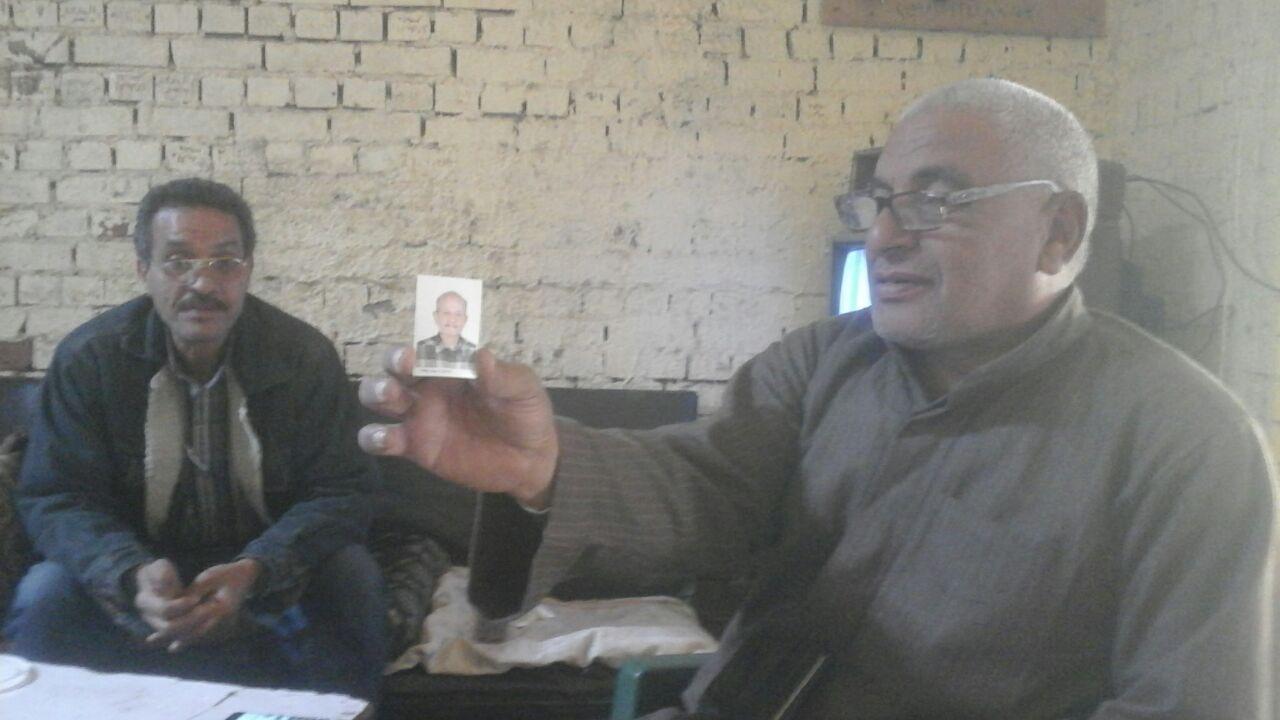 أحد أصدقاء الضحية يحمل صورته