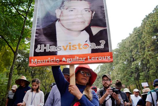 متظاهر يرفع صورة أحد ضحايا العنف