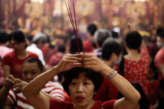 امرأة تصلي خلال احتفالات رأس السنة القمرية