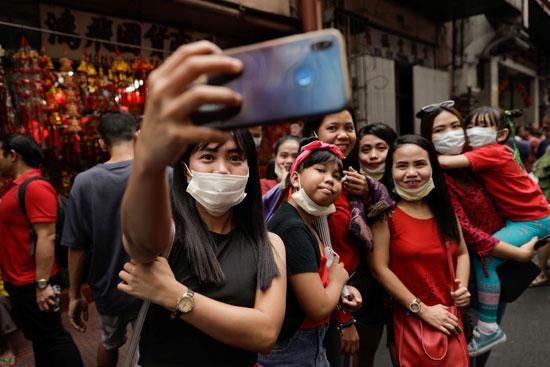 الأشخاص الذين يرتدون أقنعة واقية يأخذون صورة شخصية خلال احتفالات السنة القمرية الصينية