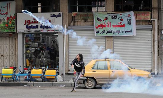 متظاهر يرمي علبة غاز مسيل للدموع على قوات الأمن العراقية