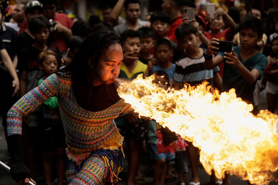 رجل ينفخ النار خلال احتفالات السنة القمرية الصينية الجديدة