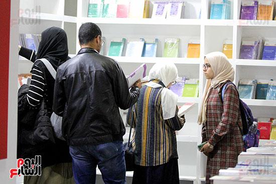 ثلاثة يبحثون  عن الكتب وواحدة تتتظر