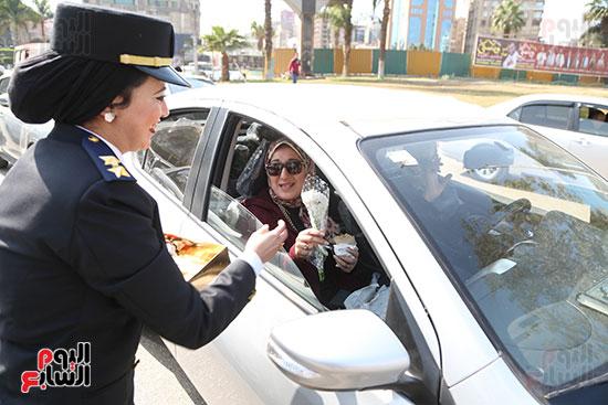 توزيع الورود والحلوى على مستقلى السيارات بميدان مصطفى محمود