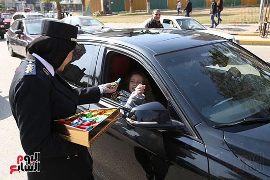 ضابطة توزع حلوى على قائدى السيارات