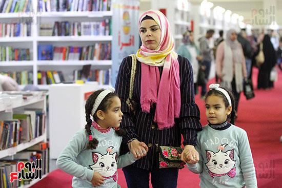 أم وطفلتاها فى المعرض