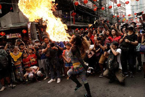 مشاهدة رجل ينفخ النار خلال احتفالات السنة القمرية الصينية الجديدة