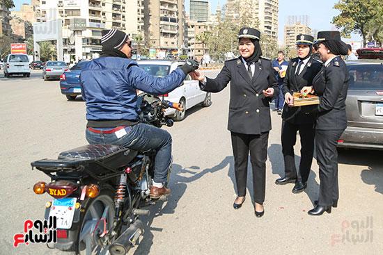 الشرطة النسائية توزع الحلوى على المواطنين