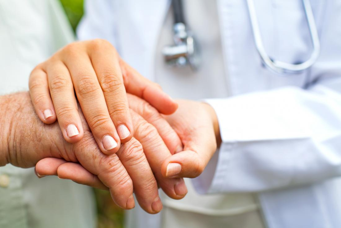 doctor-holding-older-person-s-hands-because-of-tremors-and-shakiness