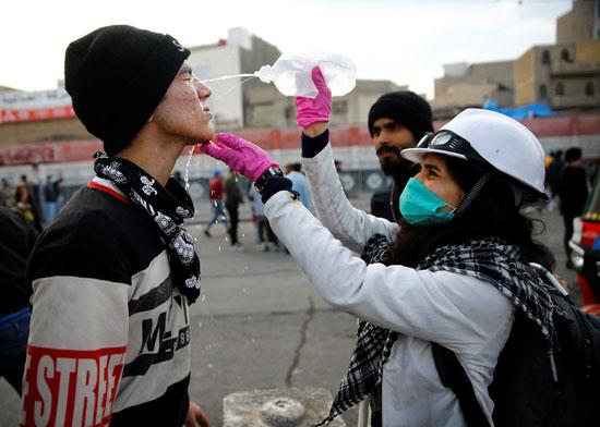 امرأة-مسعفة-تصب-سائلًا-طبيًا-على-وجه-متظاهر-أصيب-بالغاز-المسيل-للدموع