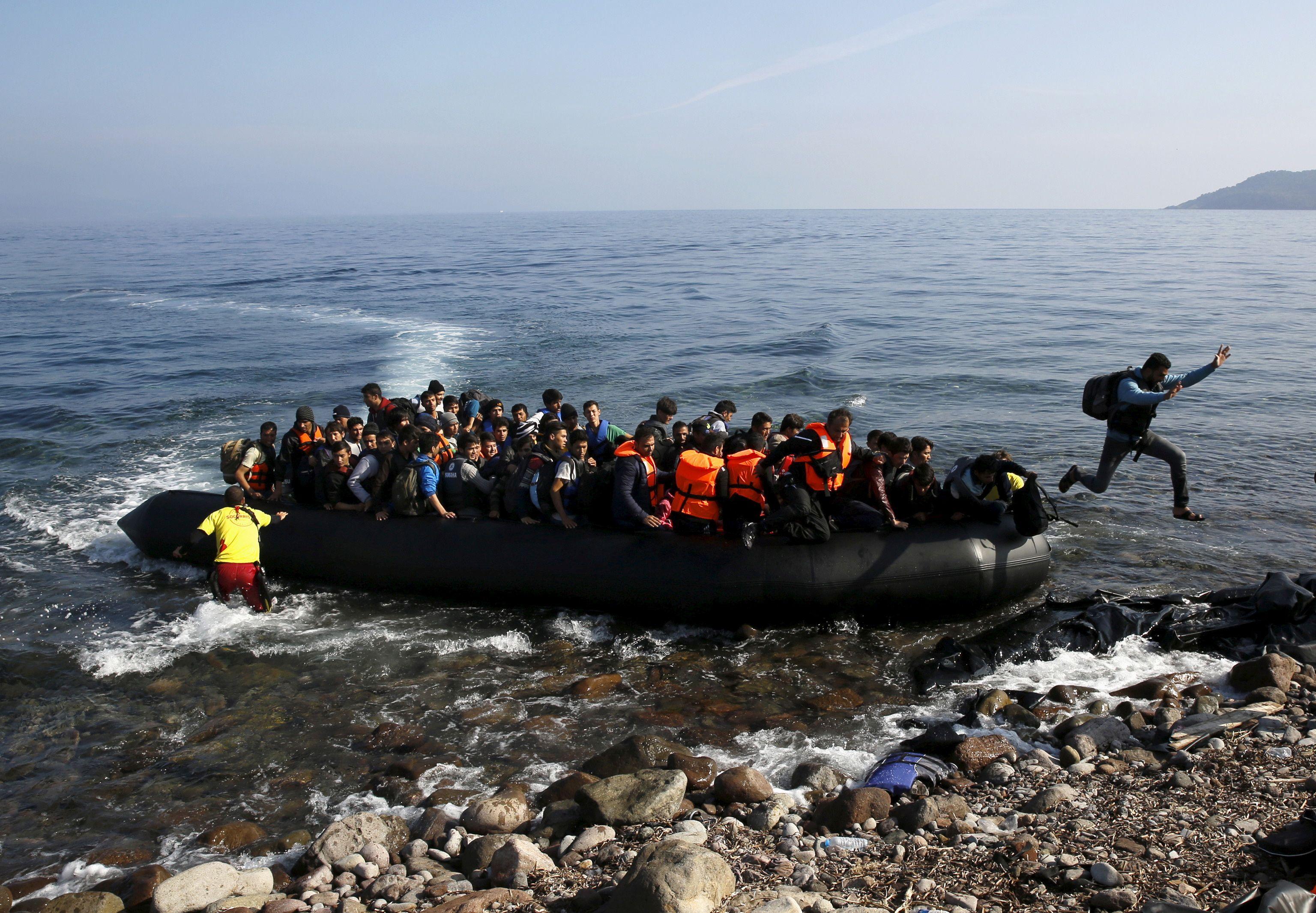 مهاجر أفغاني يقفز على طوف مكتظ على شاطئ في جزيرة ليسبوس اليونانية