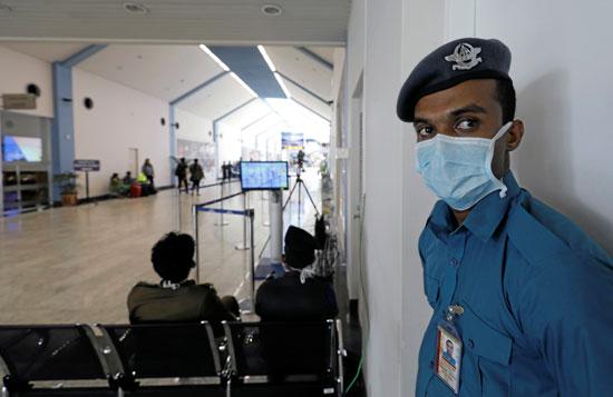 ضابط امن يرتدى القناع الواقى فى المطار