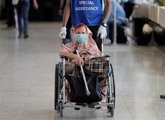 مسنة ترتدى القناع الواقى فى مطار سريلانكا