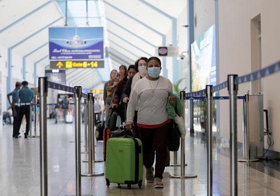 مسافرون يرتدون الاقنعة بسبب الفيروس